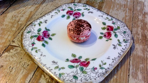 A macaron in pink, the signature Cocolicious colour, with white chocolate cream .