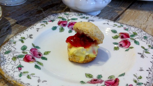 Mini scone with clotted cream and raspberry jam.
