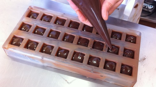 Filling milk chocolate shells with dark chocolate and pistachio ganache.