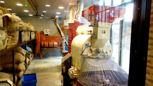 A view of La Manufacture including train-like roaster and sacks of cacao.